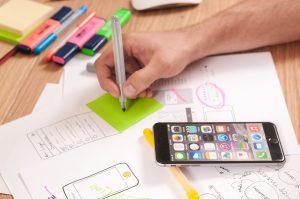 Imagem mostra uma mão desenhando sobre um postit. A mesa está com papéis que demonstram projetos e marcadores de texto. Há um Iphone sobre a mesa. Ilustra o desenvolvimento de um MVP