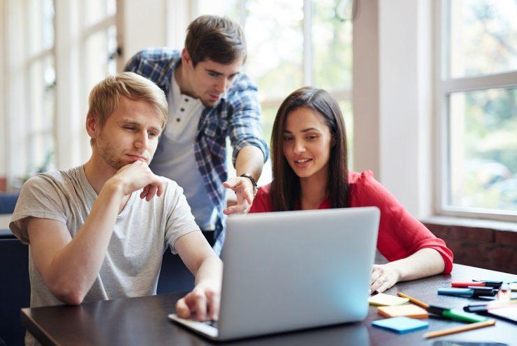 Três pessoas conversam ao redor de um notebook. Dois homens brancos e uma mulher branca, com cabelo escuro. Eles parecem atentos à tela. Ilustra o Call to Action