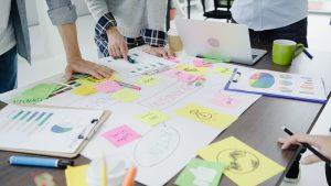Imagem mostra diversas pessoas realizando um brainstorm. Diversos papéis estão sobre a mesa, com desenhos variados. Ilustra o design thinking