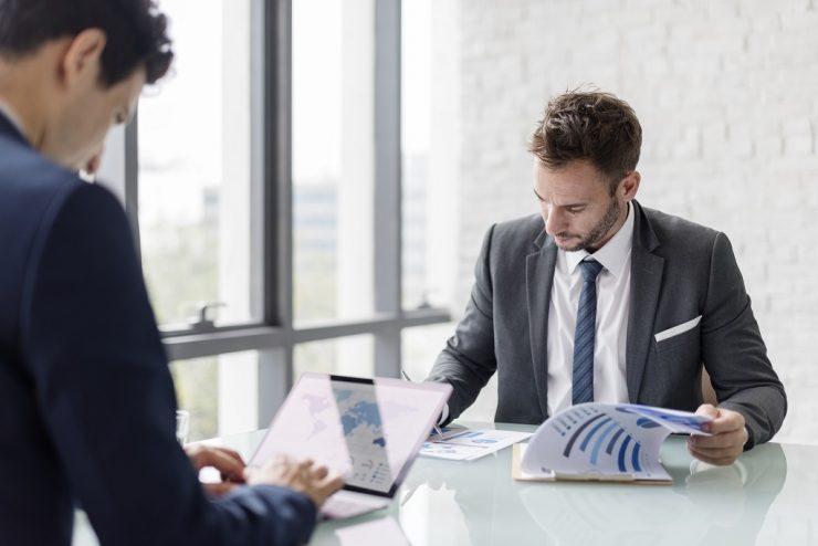 Dois homens brancos analisam dados em uma sala de reuniões. Eles trajam ternos. Um está lendo um relatório impresso, enquanto o outro utiliza um notebook. Simboliza empresa familiar