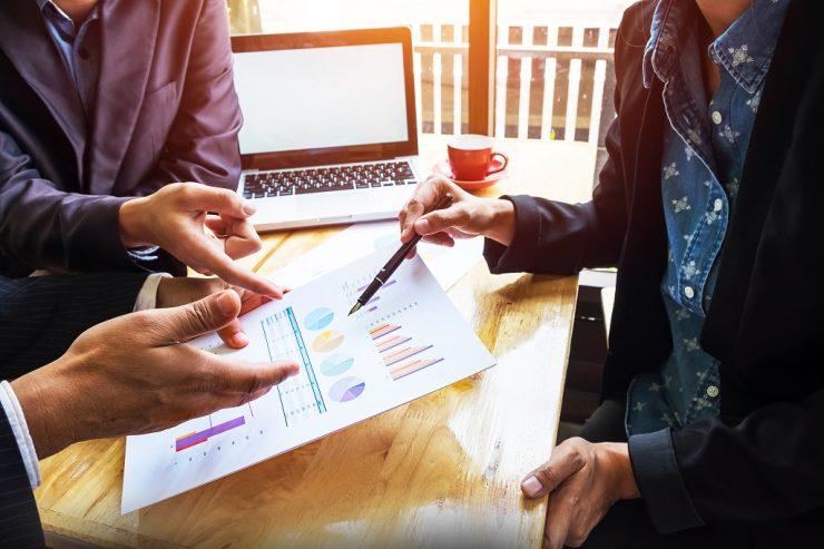 Três executivos apontam para um gráfico empresarial. Ilustra um funil de vendas