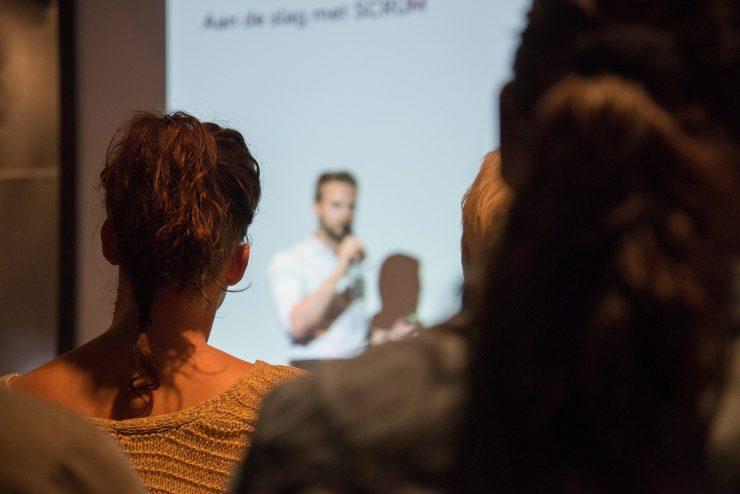 Foto mostra, ao centro, um homem branco, de blusa branca, realizando uma apresentação. Ilustra um pitch