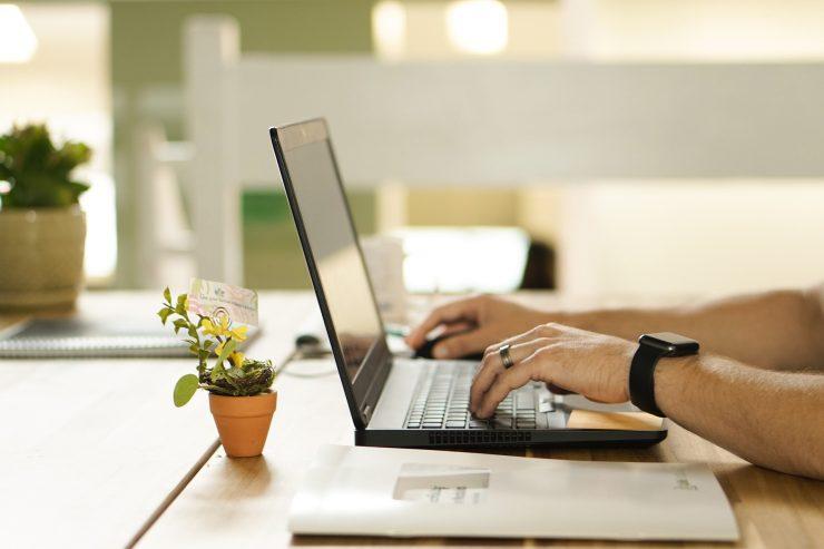 Foto mostra mãos utilizando um notebook sobre uma mesa. Simula e-mail marketing