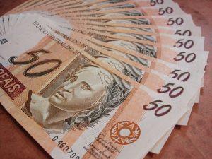 Imagem mostra várias notas de cinquenta reais. Ilustra o pagamento do 13º salário