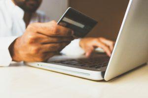 Uma mão masculina segura um cartão de crédito, enquanto utiliza um notebook sobre uma mesa. Ilustra Marketplaces