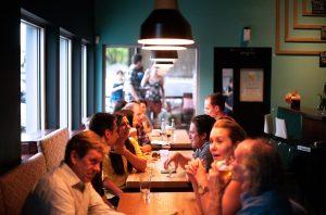 Imagem mostra várias mesas em um restaurante, como cerca de 10 pessoas conversando. Ilustra o segmento da gastronomia