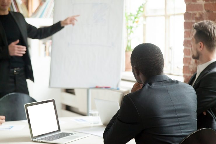 Um homem apresenta aspectos de negócios na frente de outros dois, que estão sentados. Todos usam ternos. Ilustra tipos de pitch