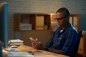 Imagem mostra um homem negro, trajando camisa azul, utilizando um celular. Ele usa óculos. Simboliza gestão em vendas.