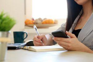 Mulher segura seu celular enquanto realiza anotações em um caderno. Ilustra o uso de aplicativos