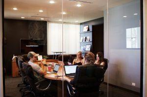 Quatro pessoas se reúnem em uma sala. Três mulheres e um homem. Eles estão ao redor de uma longa mesa e com notebooks ligados. Ilustra uma reunião de OKR.