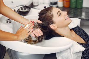 Mulher tem seu cabelo lavado em um salão de beleza