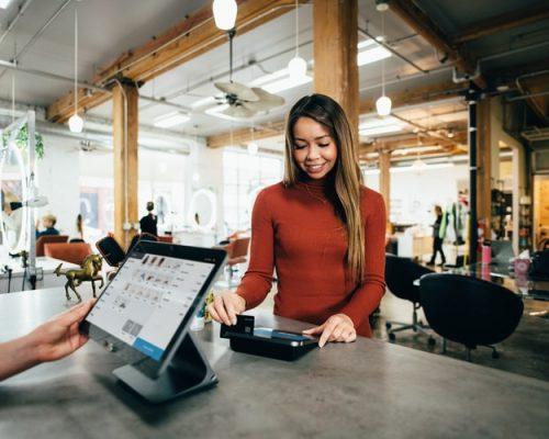 Na foto, vemos um espaço comercial, aparentemente um restaurante, com mesas e cadeiras. Em primeiro plano, há um balcão com um computador e a frente dele, uma mulher que passa um cartão de crédito em uma máquina. Ela tem cabelos claros, compridos e usa uma camisa de manga comprida bordô.