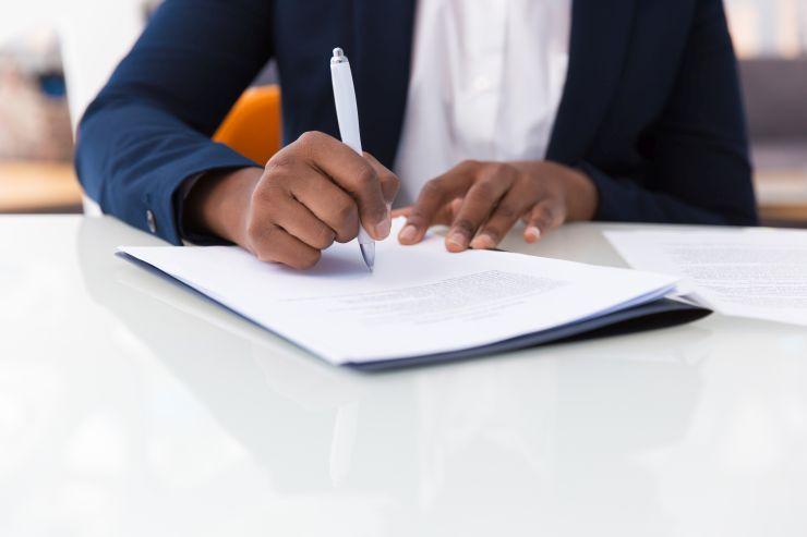 Mãos de homem negro assinando documento; Portaria regulamenta procedimentos de registro de entidades sindicais