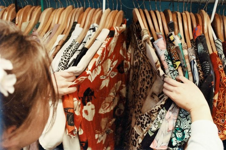 A foto mostra uma arara com diversos cabides de madeira. Os cabides têm camisas de botão estampadas de várias cores, com estampas tropicais de flores, plantas e animal print. No canto esquerdo da tela, uma mulher de cabelo claro observa as camisas, separando os cabides com as mãos para observar melhor os tecidos