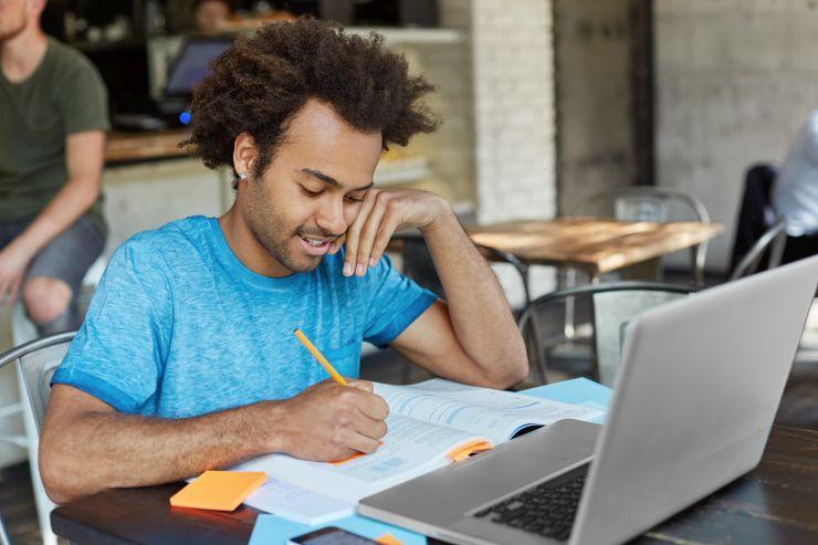 Rapaz negro fazendo anotações e estudando em frente a um notebook; cursos EAD são alternativa no período de pandemia