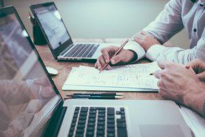 MEI - Na imagem, há uma mesa com dois notebooks abertos. Entre os computadores, há dois pares de mãos masculinas; uma das mãos segura um lápis e faz anotações em um bloco de anotações branco.