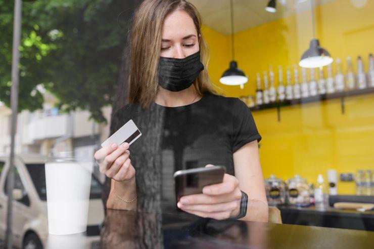 Mulher segurança cartão, com máscara facial; palestras gratuitas ajudam pequeno empreendedor