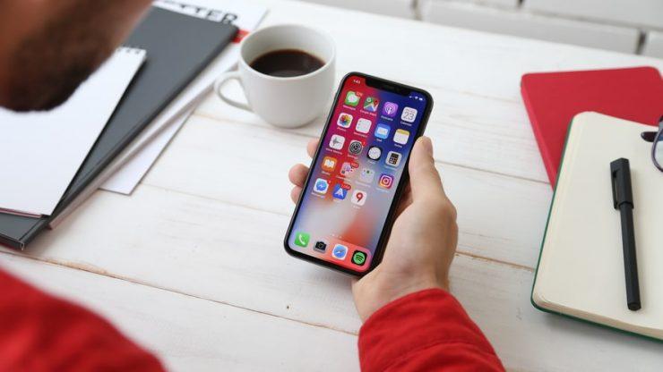 Na imagem, há uma mão (branca) segurando um celular modelo iphone XR preto. Na tela, há vários aplicativos. Ao lado esquerdo do celular, há uma xícara branca com café preto.