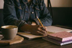 Na imagem, uma mulher escreve em um caderno com uma lápis amarelo. Só é possível ver a parte do tronco, que está vestida com uma jaqueta jeans escura. No canto direito da tela, há uma xícara de café de cor bege.