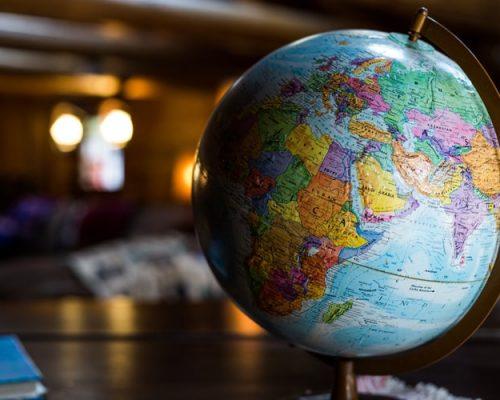 Agências de viagens: na imagem, um globo terrestre aparece em primeiro plano. Ele está em cima de uma mesa de madeira.