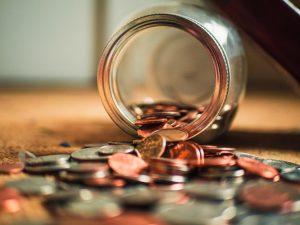 Auxílio emergencial: na imagem, há um pote de vidro despejando várias moedas de cor cobre e prata em uma mesa