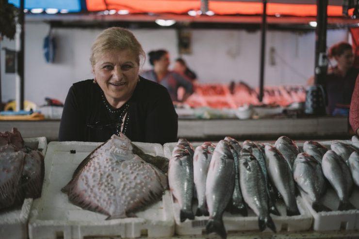 Microcrédito: na imagem, uma mulher idosa de cabelos loiros sorri para a câmera. Ela posa em frente a um balcão com vários peixes no que parece ser um mercado/feira livre.