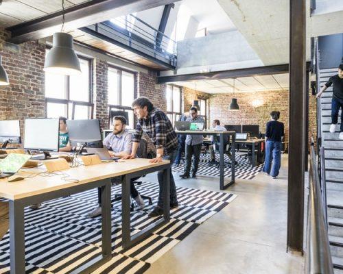 Na imagem, há uma sala ampla, típica de agências e startups, com mesas largas de madeira e alguns homens em cadeiras conversando. O ambiente é bem iluminado e possui janelas de vidro por onde entra luz natural.