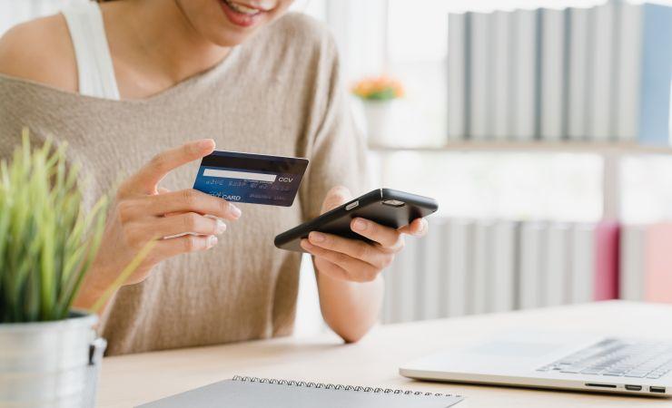 Mulher com smartphone e cartão de crédito na mão, representando Black Friday