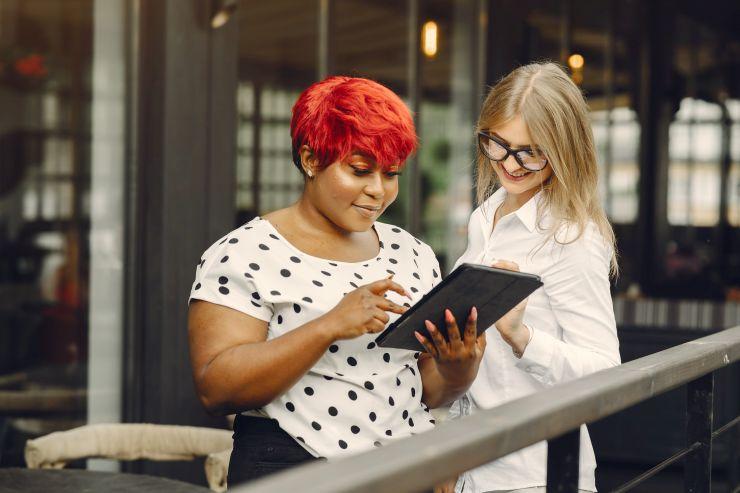 Mulheres olhando tablet - dados apontam reação mais rápida dos pequenos negócios