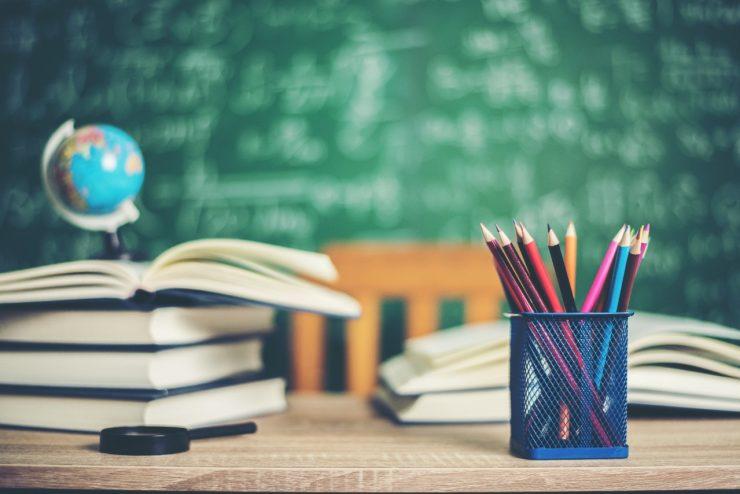 Livros abertos em cima de uma mesa, ao lado de lápis de cor, em referência ao tema gestão escolar
