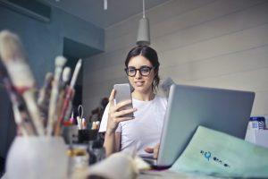 MPE: na foto, há uma mulher jovem, com camisa branca e óculos, segurando um celular. Na frente dela há um notebook, papeis e potes com acessórios de pintura e escrita.