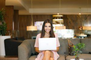 Gestão e inovação para empreendedores: uma mulher está sentada em um sofá cinza, com um notebook branco no colo, e sorri para a câmera. Ela é jovem, tem cabelos escuros e lisos e usa um vestido rosa claro.