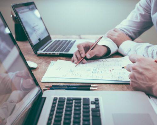 Portal do Empreendedor: na imagem, há dois notebooks abertos em uma mesa. Entre eles, há uma pessoa, aparentemente do sexo masculino, que escreve em um bloco de notas com uma caneta. Não é possível ver seu corpo, apenas seus braços, que trajam uma camisa social de cor clara.