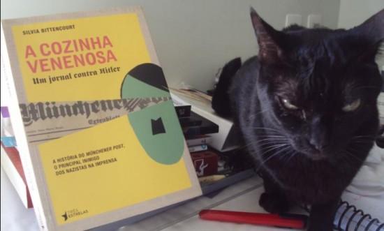 Militante dos Black Cats, a Mel pede para registrar que posou contrariada (notem a expressão) para esta resenha, pois odeia esse senhor desenhado na capa do livro. (Clique para ampliar)
