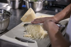 Chef rala queijo sobre uma tábua branca.