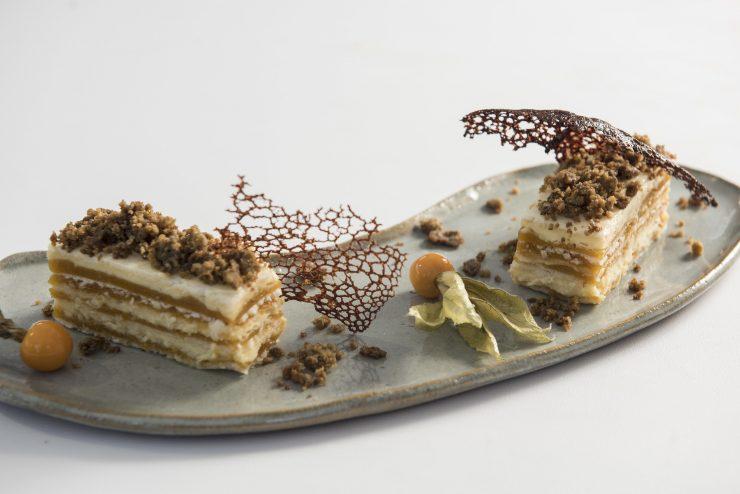 A imagem mostra duas sobremesas semelhantes, uma ao lado da outra. A sobremesa é feita em camadas, como um mil folhas, mas sem a massa folheada. Parece ser à base de doce de leite.