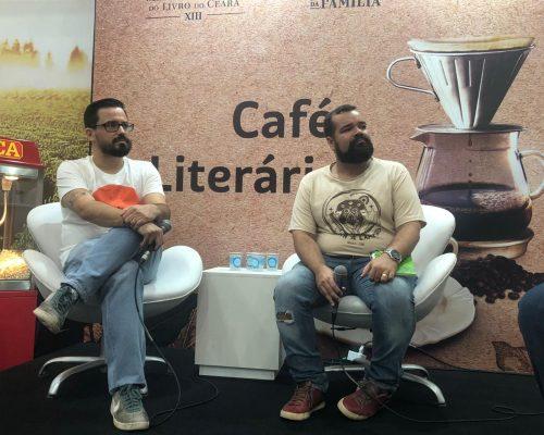 O escritor, Márcio Benjamin, de camisa branca e calça jeans, senta ao lado do autor Zé Wellington, de camisa bege e calça jeans