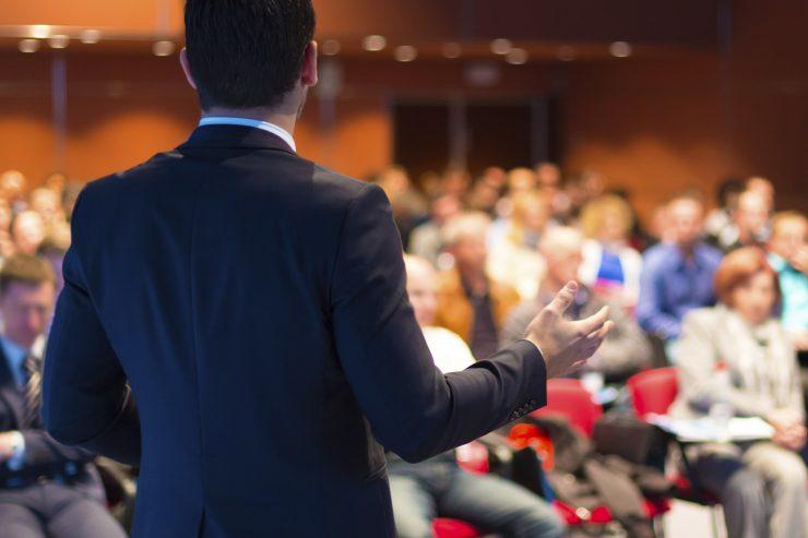 Homem de costas vestido de terno se apresenta para plateia em sua frente.