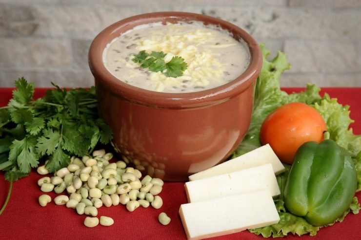 Imagem mostra uma porção de feijão verde. Ao lado do pote, legumes variados. Foto simula comida de boteco