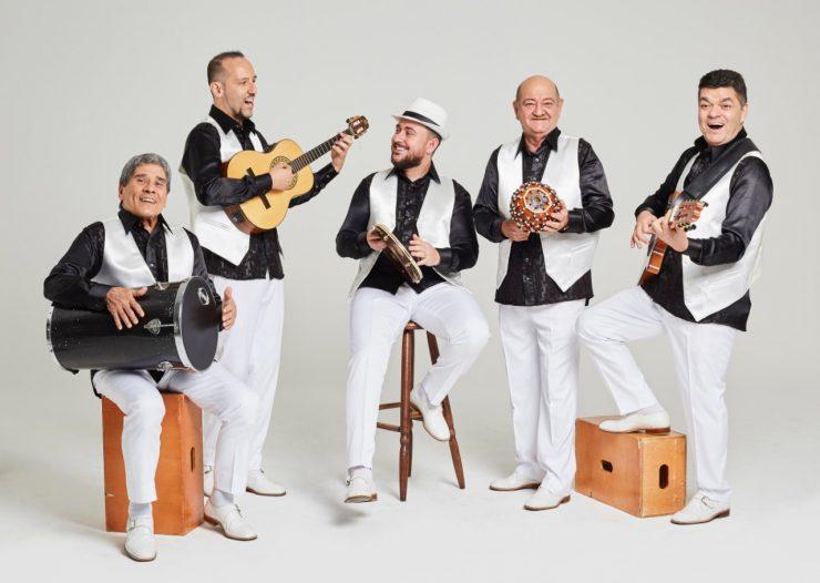 Foto do grupo Demônios da Garoa. Cinco homens em pé, com instrumentos musicais. Eles vestem roupas em preto e branco
