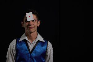 mágico à esquerda da foto com uma carta de baralho no rosto