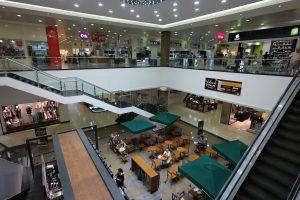 Foto mostra uma visão aberta de um shopping.