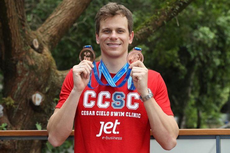 campeão olímpico César Cielo segurando duas medalhas, uma em cada mão