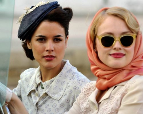 Duas mulheres, com figurino dos anos 1930, olham na direção da câmera. Uma loira, outra morena. A loira usa um lenço rosa, enquanto a morena um chapéu azul. A série é falada no idioma espanhol