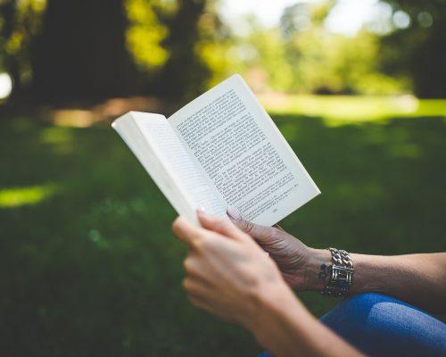 Mulher sentada em praça lê um livro