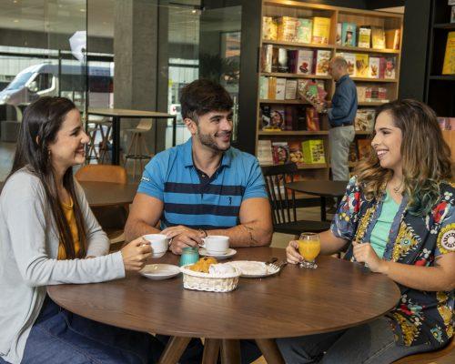 Três jovens se reúnem no Café Senac. Uma mulher à esquerda, um homem ao centro e outra mulher à direita