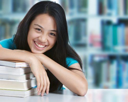 menina apoiada em livros sobre a mesa