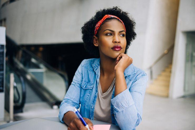 Mulher negra olha para a esquerda. Ela está segurando uma caneta e escrevendo em um papel. Ela veste uma jaqueta jeans e uma bandana vermelha na cabeça.