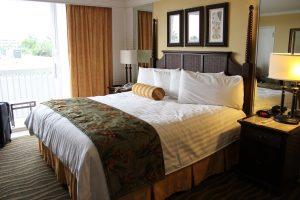 quarto de hotel com cama, crotinas e abaju