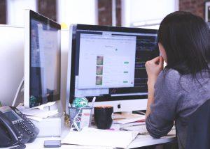 Mulher de cabelo preto olha para a tela de um computador. Parece gerir um negócio. A perspectiva da foto é pelas costas da mulher.